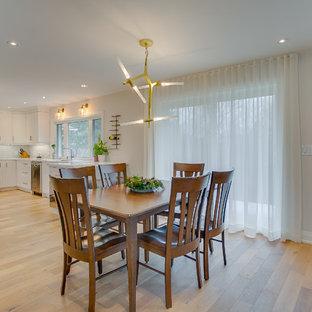 Foto di un'ampia sala da pranzo aperta verso la cucina classica con pareti bianche e pavimento in compensato