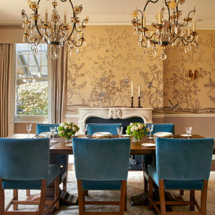 This is an example of a medium sized classic enclosed dining room in Surrey with yellow walls, dark hardwood flooring, a standard fireplace, a stone fireplace surround, brown floors and wallpapered walls.