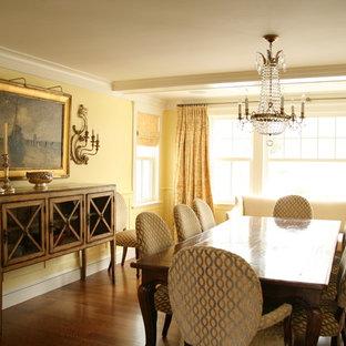 Ispirazione per una sala da pranzo classica chiusa e di medie dimensioni con pareti gialle e pavimento in compensato