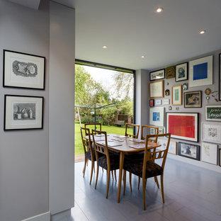 Immagine di una sala da pranzo aperta verso la cucina minimal di medie dimensioni con pareti bianche, pavimento in legno verniciato e pavimento grigio