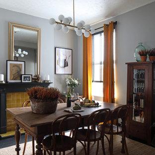 Esempio di una sala da pranzo classica chiusa e di medie dimensioni con pareti grigie, pavimento in legno verniciato, stufa a legna, cornice del camino piastrellata e pavimento nero