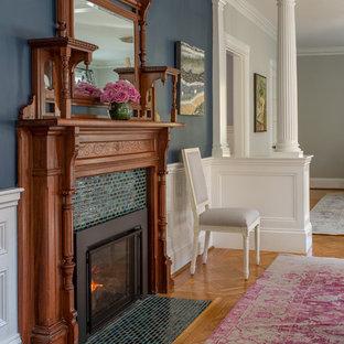 Ispirazione per una grande sala da pranzo vittoriana con camino classico, pareti blu, pavimento in legno massello medio e cornice del camino piastrellata