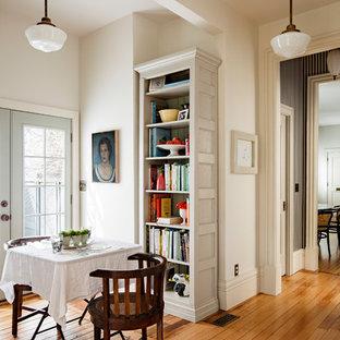 Ispirazione per una piccola sala da pranzo aperta verso la cucina vittoriana con pareti bianche, pavimento in legno massello medio, pavimento marrone e nessun camino