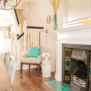 На фото: столовая в викторианском стиле с бежевыми стенами, паркетным полом среднего тона, фасадом камина из плитки и стандартным камином с