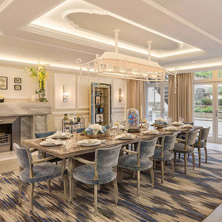 This is an example of an expansive contemporary enclosed dining room in London with beige walls, light hardwood flooring, a standard fireplace, a stone fireplace surround and brown floors.