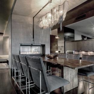 Ispirazione per una sala da pranzo aperta verso il soggiorno minimal di medie dimensioni con pareti beige, parquet scuro, camino bifacciale, cornice del camino in intonaco e pavimento marrone