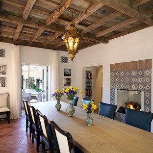 Foto di una sala da pranzo mediterranea chiusa con pareti bianche, pavimento in terracotta, cornice del camino piastrellata e pavimento arancione