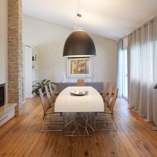 Esempio di un'ampia sala da pranzo contemporanea con pareti beige, pavimento in legno massello medio, camino classico, pavimento marrone e cornice del camino in pietra