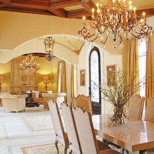 Idee per una grande sala da pranzo aperta verso il soggiorno mediterranea con pareti gialle, pavimento in gres porcellanato, camino classico e cornice del camino in pietra