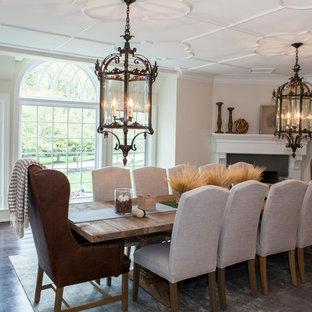 Esempio di una grande sala da pranzo chic chiusa con pareti beige, parquet scuro, camino classico e cornice del camino in pietra
