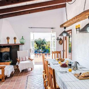Foto di una sala da pranzo aperta verso il soggiorno mediterranea con pareti bianche, pavimento in terracotta e stufa a legna