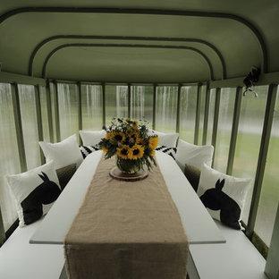 Immagine di una piccola sala da pranzo aperta verso la cucina country con pareti verdi e pavimento in laminato