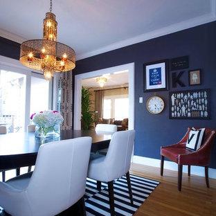 Immagine di una sala da pranzo chic con pareti nere e pavimento in legno massello medio