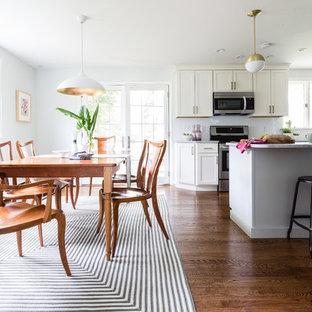Foto de comedor de cocina minimalista, pequeño, con paredes grises, suelo de madera en tonos medios, chimenea tradicional, marco de chimenea de metal y suelo marrón