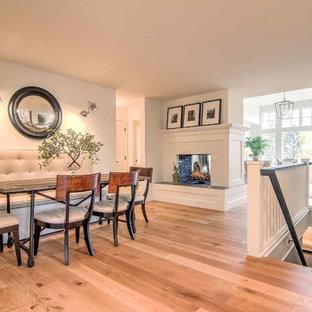 Skandinavisk inredning av ett litet kök med matplats, med vita väggar, plywoodgolv, en dubbelsidig öppen spis, en spiselkrans i tegelsten och brunt golv