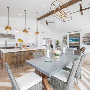 Foto de comedor de cocina de estilo de casa de campo, grande, sin chimenea, con paredes blancas, suelo de madera en tonos medios, marco de chimenea de madera y suelo marrón