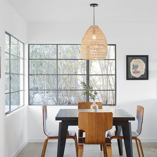 Example of a danish medium tone wood floor and brown floor dining room design in Santa Barbara with white walls