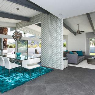 Esempio di un'ampia sala da pranzo aperta verso il soggiorno moderna con pareti bianche, pavimento in gres porcellanato, camino classico, cornice del camino piastrellata e pavimento grigio
