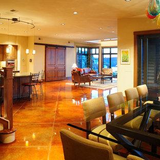 シアトルの中サイズの地中海スタイルのおしゃれなLDK (ベージュの壁、コンクリートの床、暖炉なし、赤い床) の写真