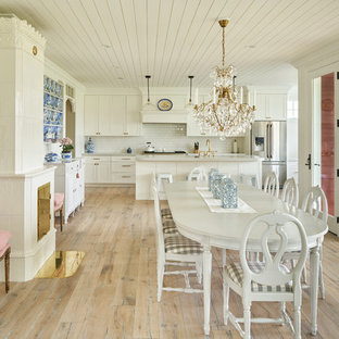 Country light wood floor kitchen/dining room combo photo in Other with white walls and a wood stove