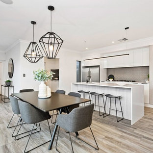 Photo of a contemporary kitchen/dining combo in Perth with white walls and light hardwood floors.