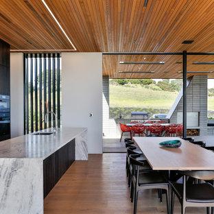 Foto på ett stort funkis kök med matplats, med vita väggar, mellanmörkt trägolv och brunt golv