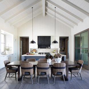 Foto di una sala da pranzo aperta verso il soggiorno country con pareti bianche, parquet scuro, pavimento marrone, soffitto a volta e pareti in perlinato