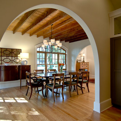 Example of a large tuscan light wood floor and brown floor enclosed dining room design in Charlotte with white walls and no fireplace