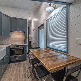 Immagine di una piccola sala da pranzo aperta verso la cucina minimalista con pareti bianche, pavimento in vinile, nessun camino e pavimento beige