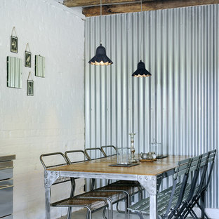 Example of an urban concrete floor dining room design in Hampshire with white walls