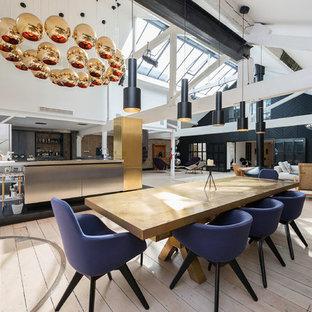 Industriell inredning av en stor matplats med öppen planlösning, med vita väggar, ljust trägolv, en hängande öppen spis och en spiselkrans i metall