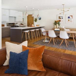 Ispirazione per una sala da pranzo aperta verso la cucina scandinava di medie dimensioni con pareti bianche, pavimento in bambù, camino classico, cornice del camino piastrellata e pavimento giallo
