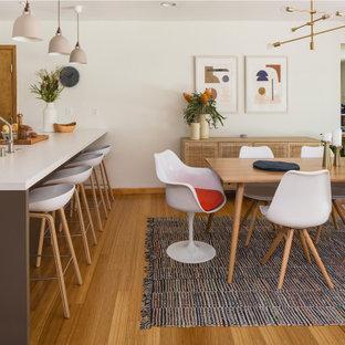 ロサンゼルスの中サイズの北欧スタイルのおしゃれなダイニングキッチン (白い壁、竹フローリング、標準型暖炉、タイルの暖炉まわり、黄色い床) の写真