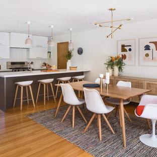 На фото: кухня-столовая среднего размера в скандинавском стиле с белыми стенами и полом из бамбука без камина с