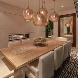 Diseño de comedor actual, de tamaño medio, cerrado, con chimenea de doble cara, paredes beige, suelo de madera clara y marco de chimenea de baldosas y/o azulejos