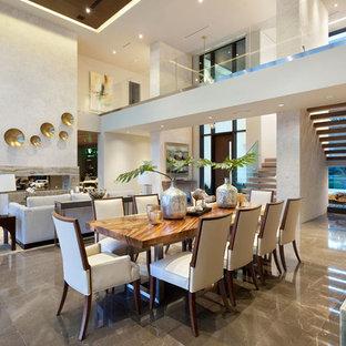 На фото: большая гостиная-столовая в стиле модернизм с бежевыми стенами, мраморным полом, горизонтальным камином и фасадом камина из камня с