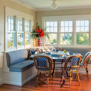 Exemple d'une salle à manger bord de mer avec une banquette d'angle, un mur blanc, un sol en bois brun, aucune cheminée, un sol marron, du lambris et boiseries.