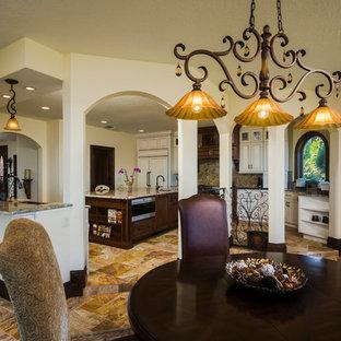 Esempio di una sala da pranzo aperta verso la cucina tradizionale di medie dimensioni con pareti beige, pavimento in ardesia, nessun camino e pavimento beige