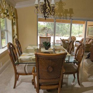 Ejemplo de comedor tropical con paredes amarillas, suelo de mármol, chimenea tradicional, marco de chimenea de yeso y suelo beige