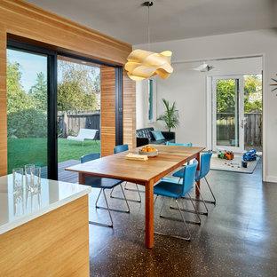 Diseño de comedor moderno, de tamaño medio, abierto, con paredes blancas y suelo de corcho