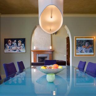 Ispirazione per una sala da pranzo design chiusa e di medie dimensioni con pareti beige, camino classico e cornice del camino in intonaco