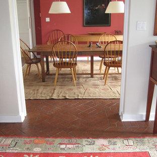 Modelo de comedor clásico renovado con paredes rojas y suelo de ladrillo