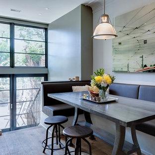 Idée de décoration pour une salle à manger design de taille moyenne avec un sol en bois clair et un mur gris.