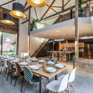 Photo of an expansive industrial open plan dining room in Hertfordshire with white walls, brown floors, exposed beams and brick walls.