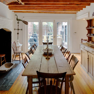 Large country medium tone wood floor enclosed dining room photo in Boston with white walls, a standard fireplace and a brick fireplace