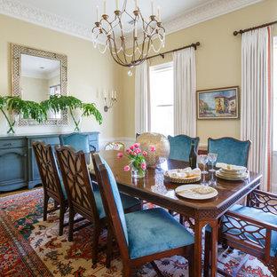 Idee per una sala da pranzo chic chiusa con pavimento in legno massello medio, nessun camino e pareti gialle