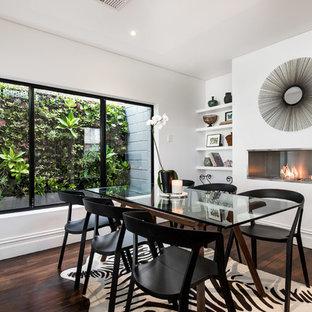 Diseño de comedor de cocina actual, pequeño, con paredes blancas, suelo de madera oscura y marco de chimenea de metal