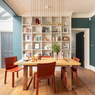 This is an example of a contemporary dining room in London with green walls, medium hardwood flooring and brown floors.