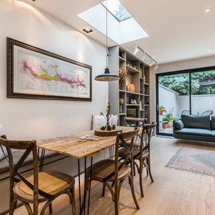 Immagine di una grande sala da pranzo aperta verso il soggiorno minimal con pareti bianche, parquet chiaro e pavimento beige
