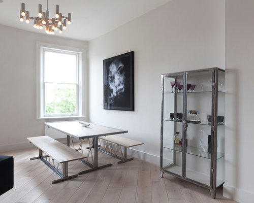 Example Of A Minimalist Medium Tone Wood Floor Dining Room Design In London  With White Walls